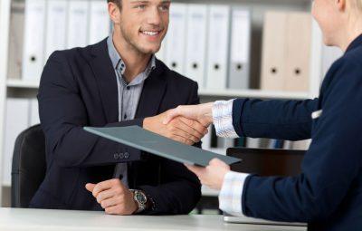 deux personnes qui se serrent la main avec un dossier