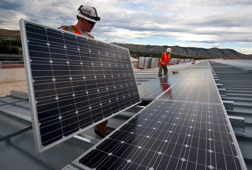 Deux ouvriers installent des panneaux solaires