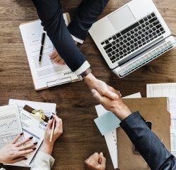 Hommes d'affaires qui se serrent la main au-dessus d'un bureau.