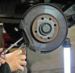 Homme qui répare la roue d'une voiture surélevée