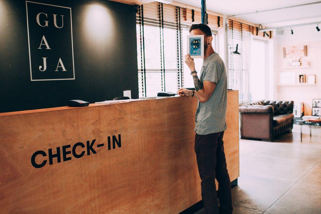 Jeune homme qui enregistre la réservation de chambre à l'accueil de l'hôtel