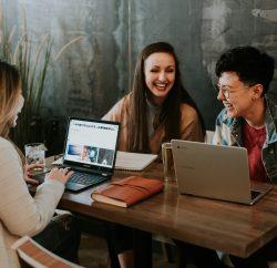 collègues assis devant leur ordinateur portable et riant ensemble