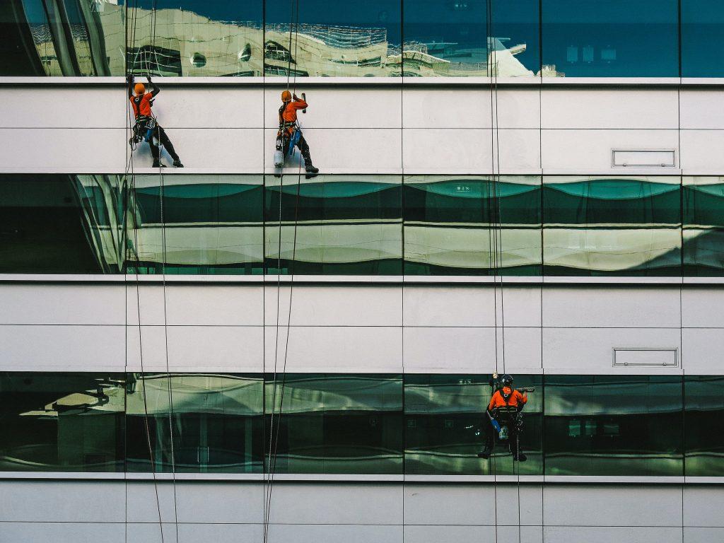 3 personnes en rappel nettoyant les fenêtres d'un immeuble