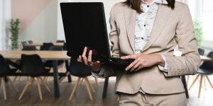 femme portant un tailleur clair avec un ordinateur portable dans les mains
